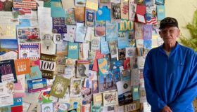 Veteran next to a wall of cards